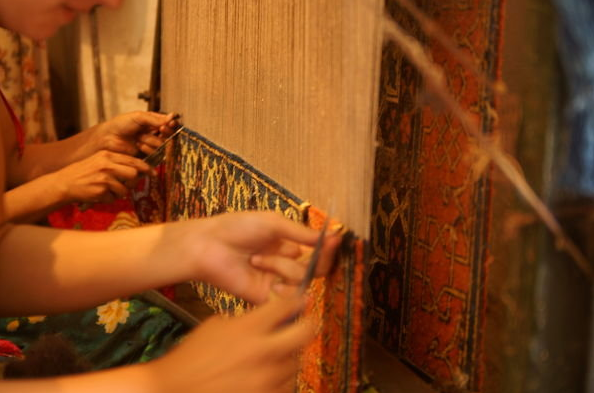 Weavers weaving a small oriental rug with a rug loom