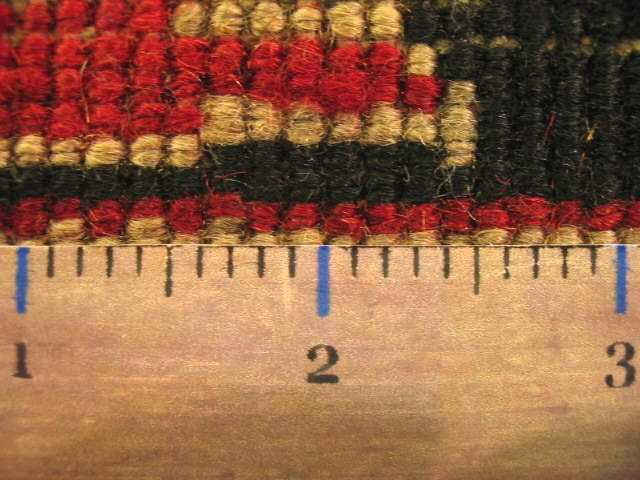 a ruler on the back of a heriz rug being used to measure the knots per square inch